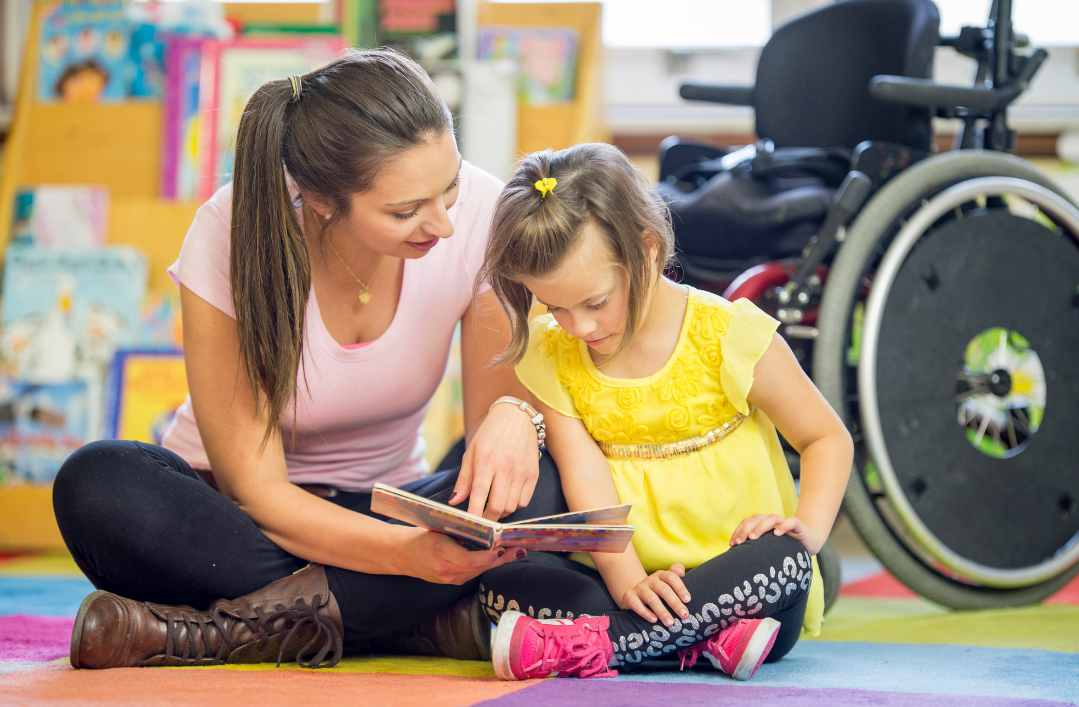 Photo of a young girl sitting on the floor reading a book with an adult. Wheelchair in the background.